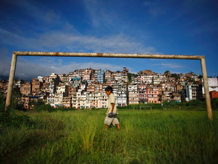 A boy walks past a football post near the ancient city of Kirtipur